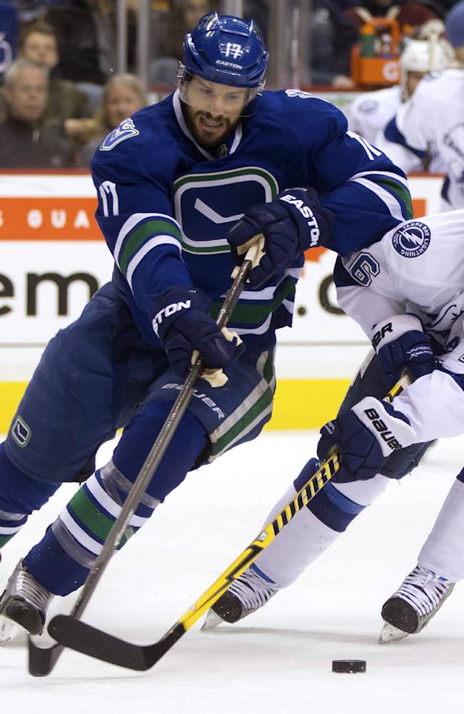 Vancouver Canucks' Ryan Kesler, left, stick-handles around Tampa Bay Lightning's Martin St. Louis defends during the first period of an NHL hockey game in Vancouver, British Columbia, on Wednesday, Jan. 1, 2014