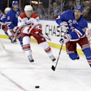 New York Rangers' Dominic Moore (28) passes the puck away from Carolina Hurricanes' Brad Malone (24) during the first period of an NHL hockey game Thursday, Oct. 16, 2014, in New York The Associated Press