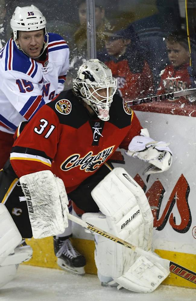 New York Rangers' Derek Dorsett, left, tries to get past Calgary Flames goalie Karri Ramo, from Finland, dduring the second period of an NHL hockey game in Calgary, Alberta, Friday, March 28, 2014
