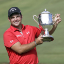 Patrick Reed holds up the Sam Snead trophy after he won the Wyndham Championship golf tournament in a second hole playoff at the Sedgefield Coun