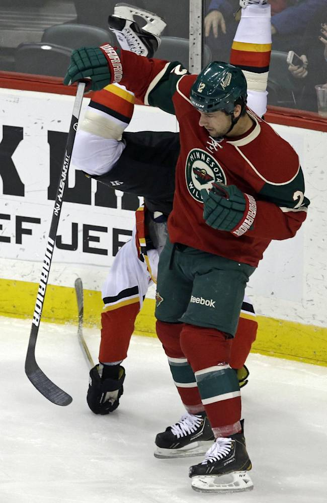 Calgary Flames' Brian McGrattan flips Minnesota Wild's defenseman Keith Ballard during the first period of an NHL hockey game, Tuesday, Nov. 5, 2013, in St. Paul, Minn