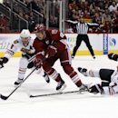 Phoenix Coyotes right wing David Moss (18) carries the puck between Chicago Blackhawks defenseman Duncan Keith (2) and Brent Seabrook (7) in the second period of an NHL hockey game on Saturday, Nov. 30, 2013, in Glendale, Ariz The Associated Press