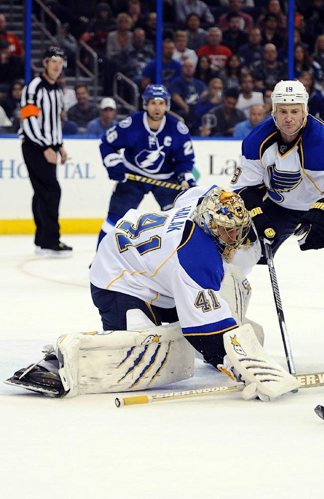 St. Louis Blues defenseman Jay Bouwmeester, center, looks on as Blues St. Louis Blues goalie Jaroslav Halak, left, of Slovakia, defends the goal from a shot by Tampa Bay Lightning left wing Ryan Malone during the second period of an NHL hockey game Saturday, Nov. 2, 2013, in Tampa, Fla