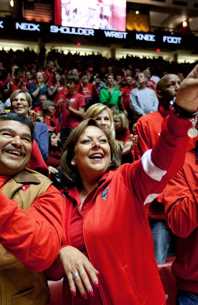 New Mexico Governor Susana Martinez, center, attends the New Mexico vs Alabama A&M NCAA basketball with her husband Chuck Franco, left, and advisor Jay McCleskey in Albuquerque, N.M., Saturday, Nov. 9, 2013. New Mexico won 88-52