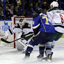 Minnesota Wild goalie Niklas Backstrom, of Finland, deflects the puck as teammate Marco Scandella (6) and St. Louis Blues' T.J. Oshie, center, watch during the second period of an NHL hockey game Monday, Nov. 25, 2013, in St. Louis The Associated Press