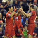 Liverpool's Luis Suarez, left, celebrates with teammate Steven Gerrard after scoring the fourth goal of the game during their English Premier League soccer match against Norwich City at Anfield in Liverpool, England, Wednesday Dec. 4, 2013
