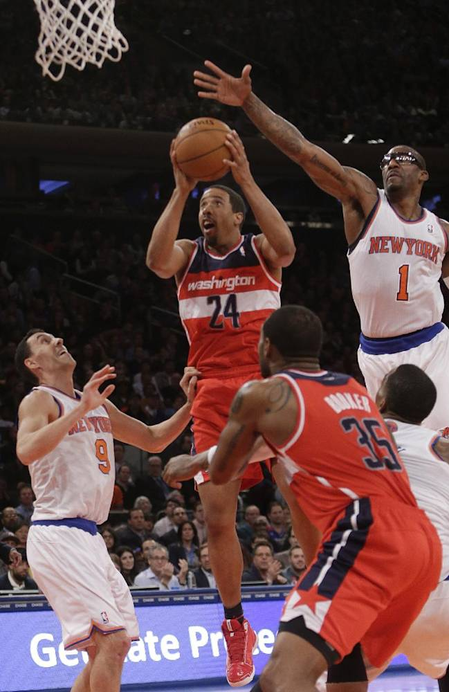 Washington Wizards' Andre Miller (24) drives past New York Knicks' Pablo Prigioni (9) and Amar'e Stoudemire (1) during the second half of an NBA basketball game Friday, April 4, 2014, in New York. The Wizards won the game 89-90
