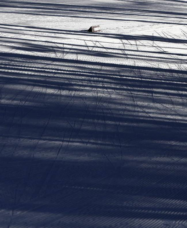 A skier is silhouetted during a biathlon training session at the 2014 Winter Olympics, Friday, Feb. 7, 2014, in Krasnaya Polyana, Russia