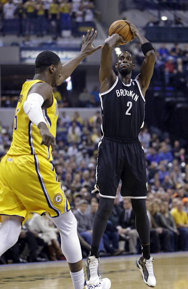 Brooklyn Nets forward Kevin Garnett, right, shoots over Indiana Pacers center Roy Hibbert in the first half of an NBA basketball game in Indianapolis, Saturday, Feb. 1, 2014