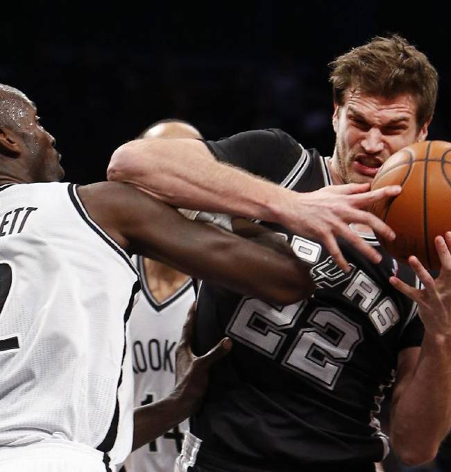 San Antonio Spurs' Tiago Splitter (22), of Brazil, is fouled by Brooklyn Nets' Kevin Garnett (2) during the first half of an NBA basketball game on Thursday, Feb. 6, 2014, in New York