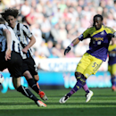 Swansea City's Marvin Emnes, right, has a shot towards goal past Newcastle United's captain Fabricio Coloccini, left, during their English Premier League soccer match at St James' Park, Newcastle, England, Saturday, April 19, 2014