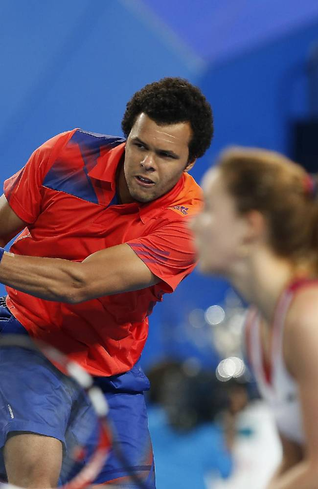 Jo-Wilfried Tsonga of France, left, plays a backhand shot while mixed doubles partner Alize Cornet, right, looks on against Agnieszka Radwanska and Grzegorz Panfil of Poland during the mixed doubles final, Saturday, Jan. 4, 2014, at the Hopman Cup tennis tournament in Perth Australia