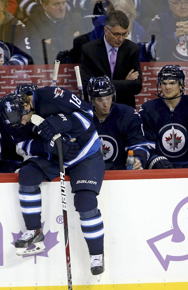 Winnipeg Jets' Bryan Little (18) sits on the boards during the break during a break before a shootout against the Washington Capitals in an NHL hockey game in Winnipeg, Manitoba, Tuesday, Oct. 22, 2013. The Capitals won 5-4 in a shootout. Jets head coach Claude Noel watches in the background