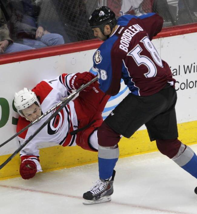 Colorado Avalanche left wing Patrick Bordeleau (58) checks Carolina Hurricanes defenseman Andrej Sekera (4), of Slovakia, in the third period of a hockey game in Denver on Friday, Oct. 25, 2013. Bordeleau was penalized for boarding on the hit. Colorado won 4-2