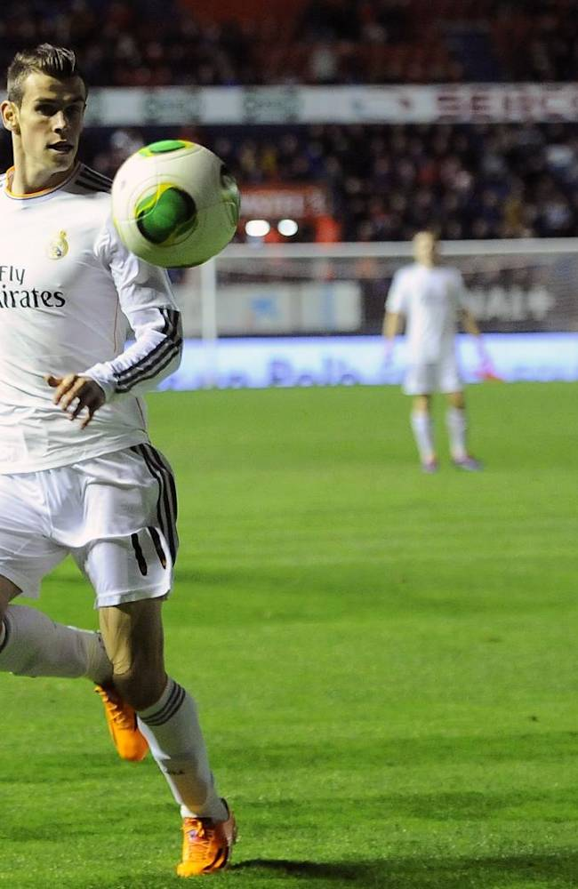 Real Madrid's Gareth Bale of Wales goes for the ball during their Spanish Copa del Rey round-16 second leg soccer match between Osasuna and Real Madrid , at El Sadar stadium, in Pamplona northern Spain on Wednesday, Jan. 15, 2014
