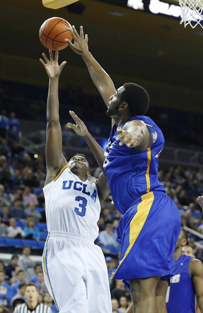 UCLA's Jordan Adams, left, shoots as UC Santa Barbara's Alan Williams, right, defends during the second half of an NCAA college basketball game, Tuesday, Dec. 3, 2013, in Los Angeles. UCLA won 89-76