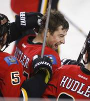 Calgary Flames' Chris Butler, center, is congratulated by teammates after scoring the winning goal during overtime in NHL hockey action in Calgary, Alberta, Thursday, Dec. 12, 2013. The Calgary Flames beat the Carolina Hurricanes 2-1. (AP Photo/The Canadian Press, Jeff McIntosh)