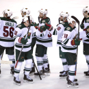 Members of the Minnesota Wild celebrate their 4-2 win over the Vancouver Canucks following the third period of NHL action in Vancouver, British Columbia, Sunday, Feb. 1, 2015 The Associated Press