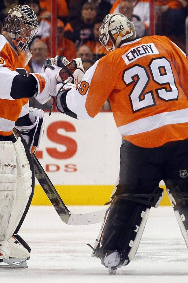 Philadelphia Flyers goalie Steve Mason, left, taps gloves with Ray Emery as he leaves the game in the second period of an NHL hockey game with the Washington Capitals, Friday, Nov. 1, 2013, in Philadelphia. Mason gave up three goals before being pulled mid-way through the period