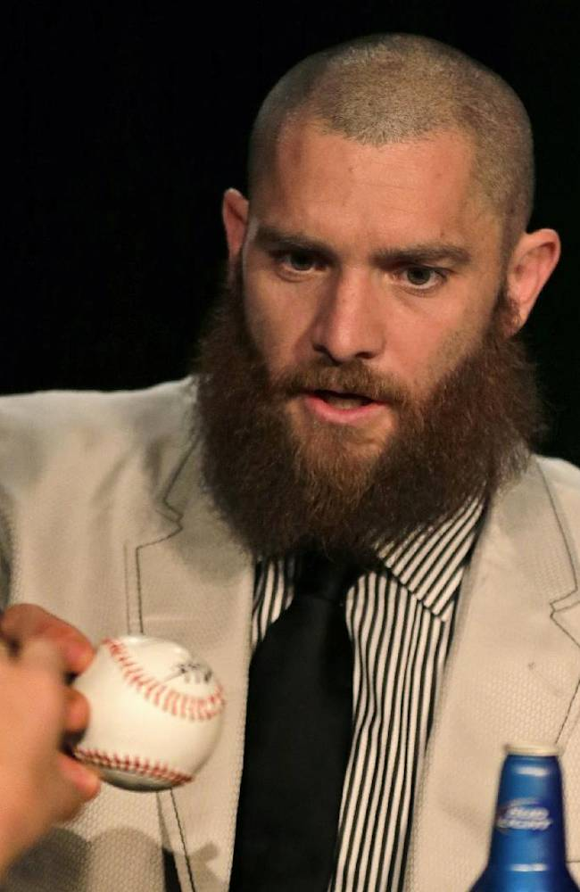 Boston Red Sox outfielder Jonny Gomes gives a baseball back to a fan after signing an autograph before the 75th annual dinner of the Boston chapter of the Baseball Writers' Association of America in Boston, Thursday, Jan. 23, 2014. Gomes, the bandleader of the beard brigade during Boston's run to the 2013 World Series title, said he will be shaving his off before spring training so that he can file it