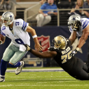 Dallas Cowboys quarterback Tony Romo (9) escapes from New Orleans Saints defensive end Tyrunn Walker (75) during the second half of an NFL football game Sunday, Sept. 28, 2014, in Arlington, Texas. NBC's
