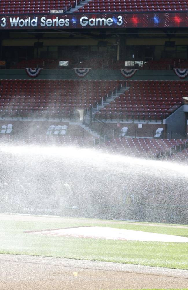 A grounds crew worker waters the field before a baseball practice, Friday, Oct. 25, 2013, in St. Louis. The St. Louis Cardinals and Boston Red Sox are set to play Game 3 of the World Series on Saturday in St. Louis