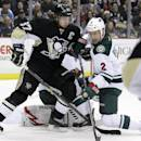 Minnesota Wild's Keith Ballard (2) tries to clear Pittsburgh Penguins' Sidney Crosby (87) from in front of Wild goalie Niklas Backstrom, behind, during the second period of an NHL hockey game in Pittsburgh, Thursday, Dec. 19, 2013. (AP Photo/Gene J. Puskar)