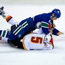Vancouver Canucks' Kevin Bieksa, top, falls on Calgary Flames' Mark Giordano as they fight during the first period of an NHL hockey game, Saturday, March 8, 2014 in Vancouver, British Columbia The Associated Press