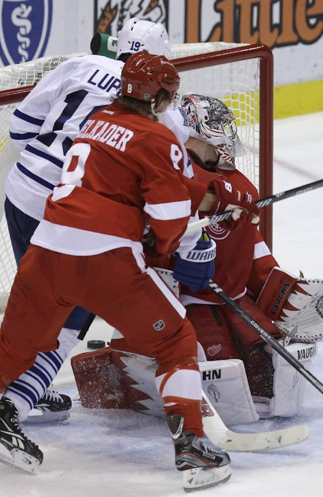 Toronto Maple Leafs right wing Joffrey Lupul (19), defended by Detroit Red Wings left wing Justin Abdelkader (8) gets the puck past goalie Jimmy Howard for a goal during the second period of an NHL hockey game in Detroit, Friday, Sept. 27, 2013