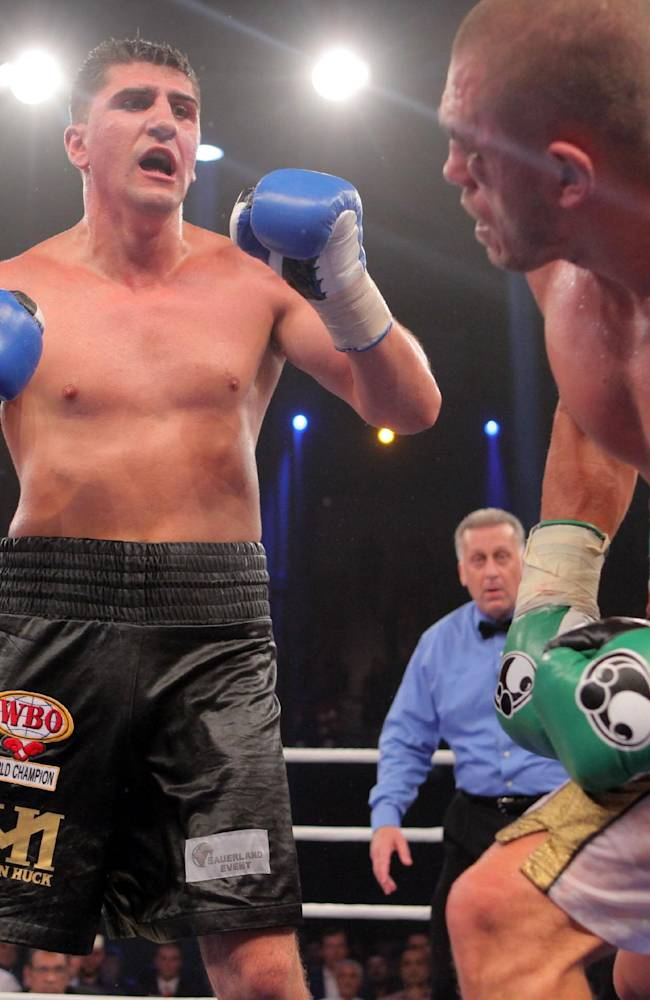 In  this picture taken Saturday Aug. 30, 2014 German boxer Marco Huck, left, knocks down Italian challenger Mirko Larghetti during their WBO cruiserweight title bout in Halle, western Germany.  German defending cruiserweight champion  Marco Huck defeated Mirko Larghetti of Italy by unanimous decision Saturday to retain his WBO belt for the record-equaling 13th time