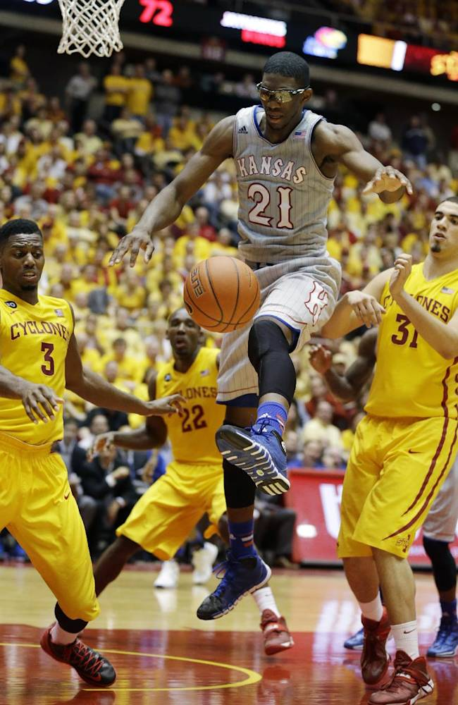 Kansas center Joel Embiid (21) loses the ball between Iowa State's Melvin Ejim, left, and Georges Niang, right, during the second half of an NCAA college basketball game, Monday, Jan. 13, 2014, in Ames, Iowa. Kansas won 77-70