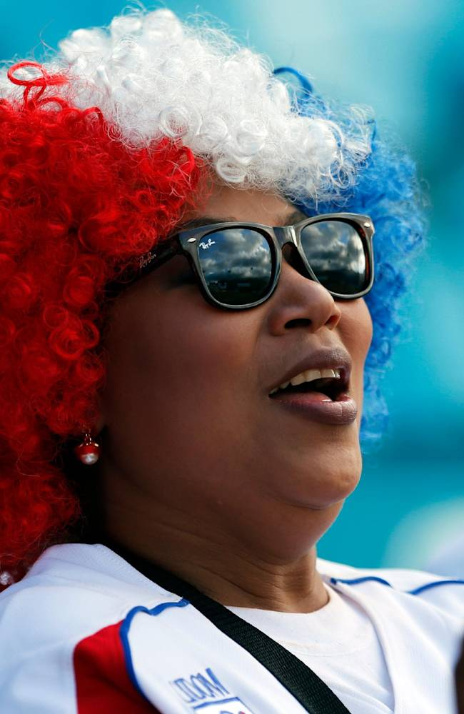 A fan of the Dominican Republic cheers her team during a Caribbean Series baseball game against Cuba in Porlamar, Venezuela, Monday, Feb. 3, 2014