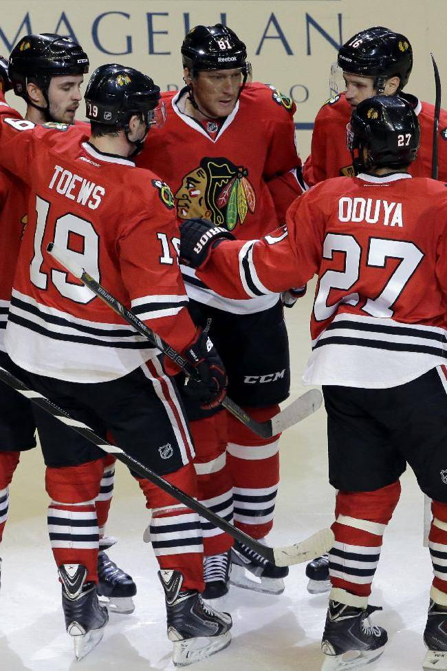 Chicago Blackhawks' Marian Hossa, center, celebrates with teammates after scoring his second goal, during the third period of an NHL hockey game against the Anaheim Ducks in Chicago, Friday, Jan. 17, 2014. The Blackhawks won 4-2