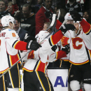 Calgary Flames defenseman Dennis Wideman, right, is mobbed by teammates as they celebrate a review of his shot giving him a goal against the Los Angeles Kings in overtime of an NHL hockey game to give the Flames the victory, Monday, Jan. 19, 2015, in Los