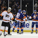 New York Islanders left wing Nikolay Kulemin (86), center Brock Nelson (29) and right wing Michael Grabner (40) celebrate Kulemin's goal as Philadelphia Flyers center Vincent Lecavalier (40) skates away in the first period of an NHL hockey game at Nassau