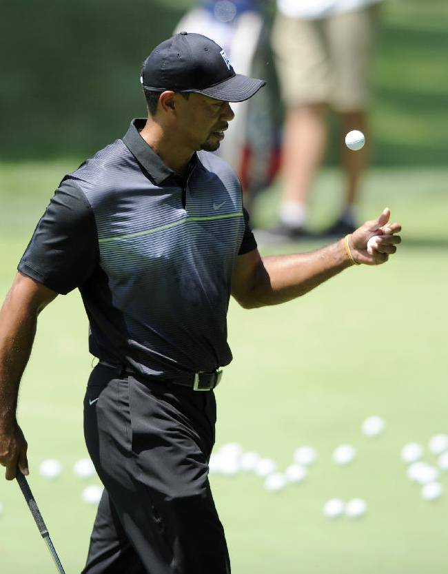 Tiger Woods tosses a ball around during practice for the Quicken Loans National golf tournament, Tuesday, June 24, 2014, in Bethesda, Md
