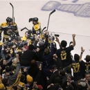 Fans and teammates celebrate as they swarm around Boston Bruins center Patrice Bergeron, who scored the game winning goal off
