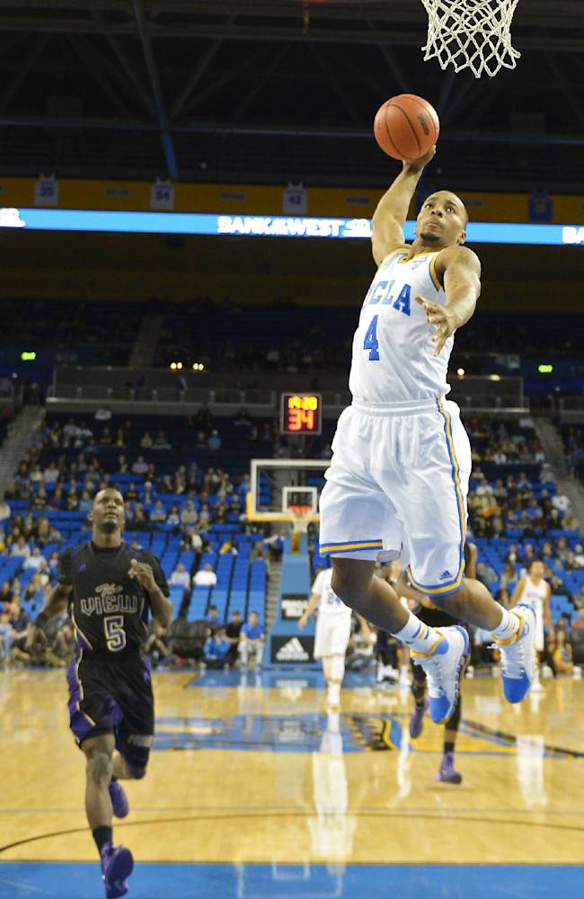 UCLA guard Norman Powell (4) goes up for a dunk as Prairie View guard Tre Hagood (5) gives chase during the first half of an NCAA college basketball game, Saturday, Dec. 14, 2013, in Los Angeles