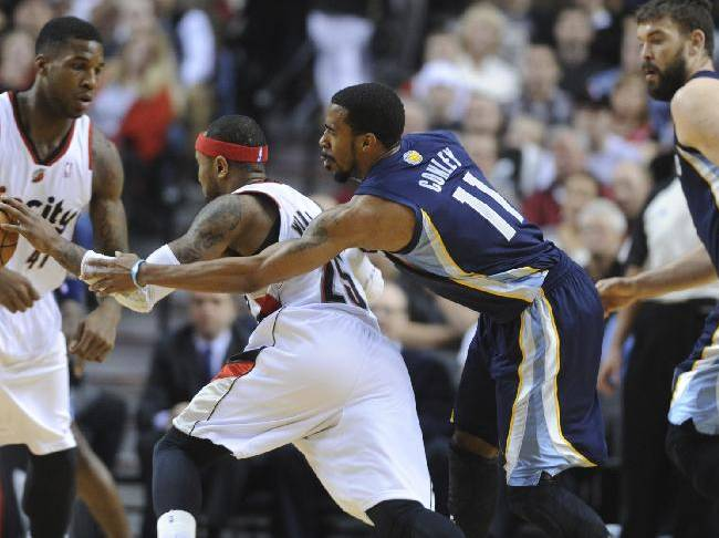 Memphis Grizzlies' Mike Conley (11) knocks the ball away from Portland Trail Blazers' Mo Williams (25) during the first half of an NBA basketball game in Portland, Ore., Sunday March 30, 2014