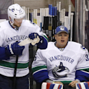 After a trade of Vancouver Canucks goalie Roberto Luongo, Canucks reserve goalie Pat Conacher, right, sits on the bench next to Alexander Edler (23), of Sweden, and Dan Hamhuis (2) during the third period of an NHL hockey game against the Phoenix Coyotes