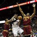 Atlanta Hawks power forward Paul Millsap (4) drives between Cleveland Cavaliers' C.J. Miles, lfet, and Andrew Bynum (21) in the first half of an NBA basketball game Friday, Dec. 6, 2013, in Atlanta The Associated Press