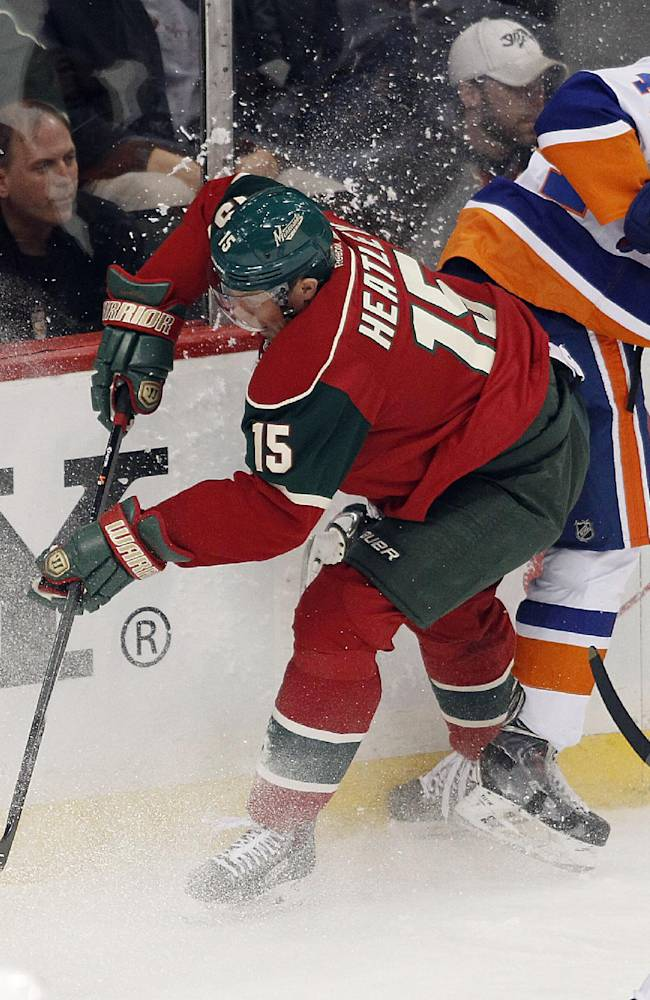 Minnesota Wild defenseman Dany Heatly (15) and New York Islanders defensman Calvin De Haan battle for the puck during the first period of their NHL hockey game, Sunday Dec. 29, 2013, in St. Paul, Minn