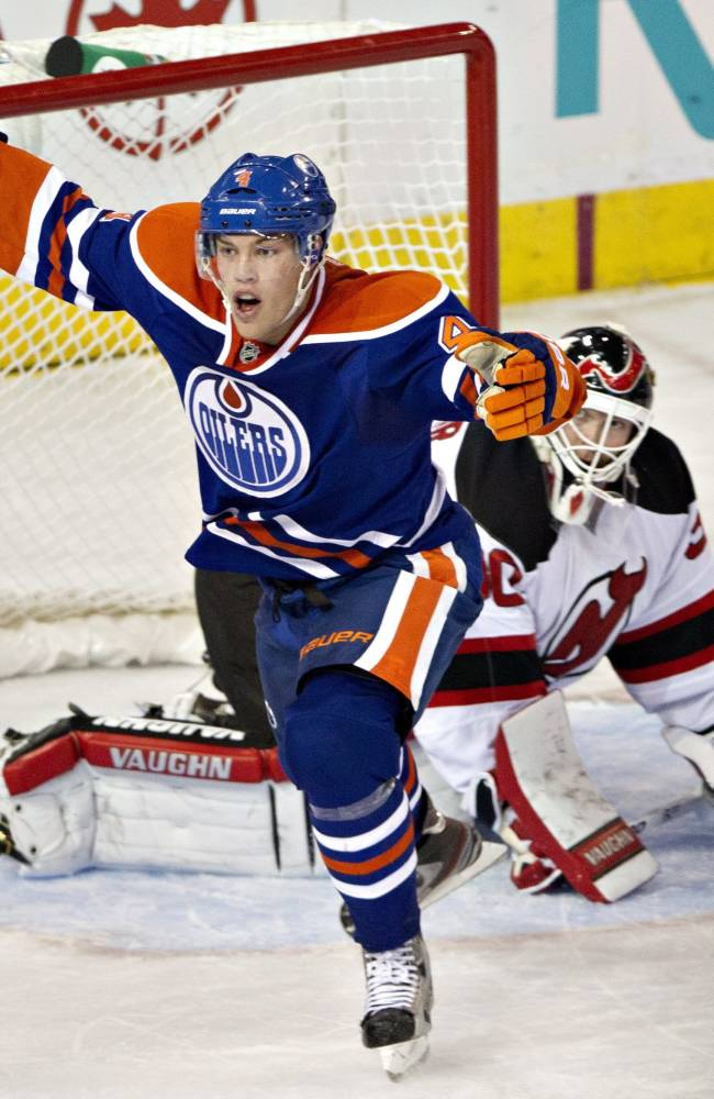 New Jersey Devils goalie Martin Brodeur (30) looks up as Edmonton Oilers' Taylor Hall (4) celebrates a goal during the third period of an NHL hockey game Monday, Oct. 7, 2013, in Edmonton, Alberta. The Oilers won 5-4 in a shootout