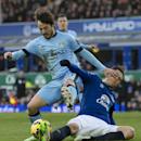Manchester City's David Silva, left, fends off a tackle by Everton's Muhamed Besic during the English Premier League soccer match between Everton and Manchester City at Goodison Park Stadium, Liverpool, England, Saturday Jan. 10, 2015