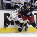 Columbus Blue Jackets' Jared Boll, right, checks Nashville Predators' Joonas Rask, of Finland, during the first period of an