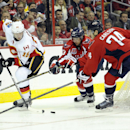 Calgary Flames defenseman Ladislav Smid (15), of the Czech Republic, tries to get the puck past Washington Capitals defenseman John Carlson (74) and Jay Beagle (83) during the second period of an NHL hockey game, Tuesday, Nov. 4, 2014, in Washington The A