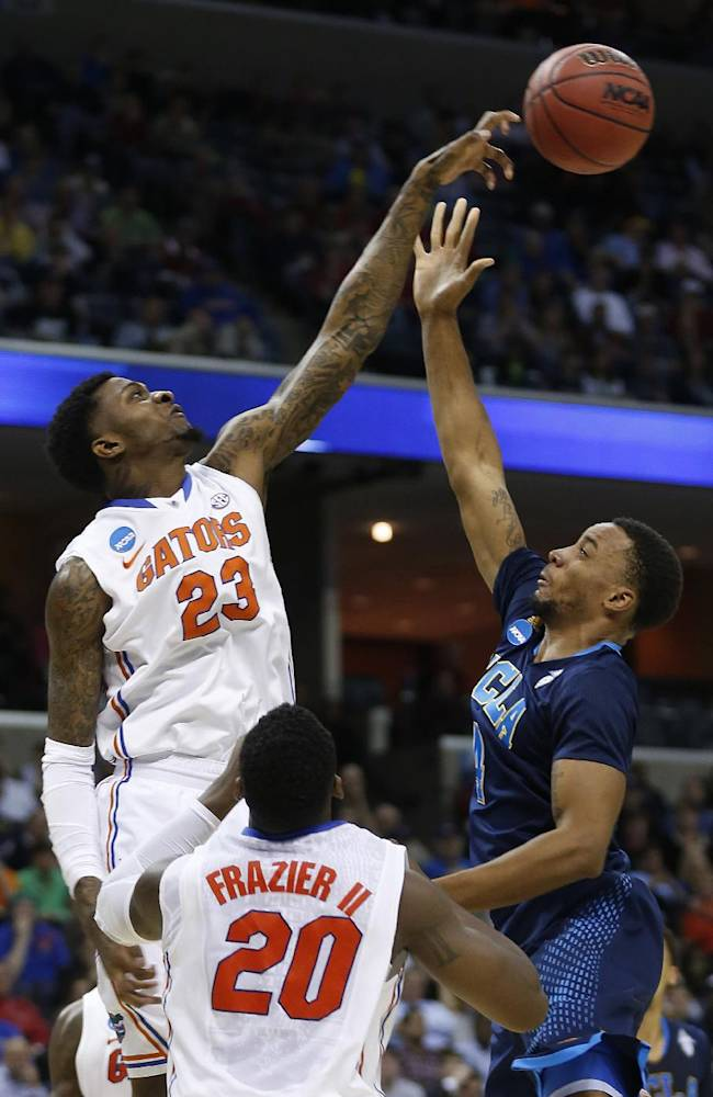 Florida's Chris Walker (23) blocks the shot by UCLA guard Norman Powell (4) during the first half in a regional semifinal game at the NCAA college basketball tournament, Thursday, March 27, 2014, in Memphis, Tenn
