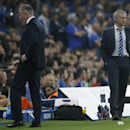 Schalke's head coach Jens Keller walks back to the bench as Chelsea's manager Jose Mourinho keeps watching the Champions League group G soccer match between Chelsea and Schalke 04 at Stamford Bridge stadium in London, Wednesday, Sept. 17, 2014