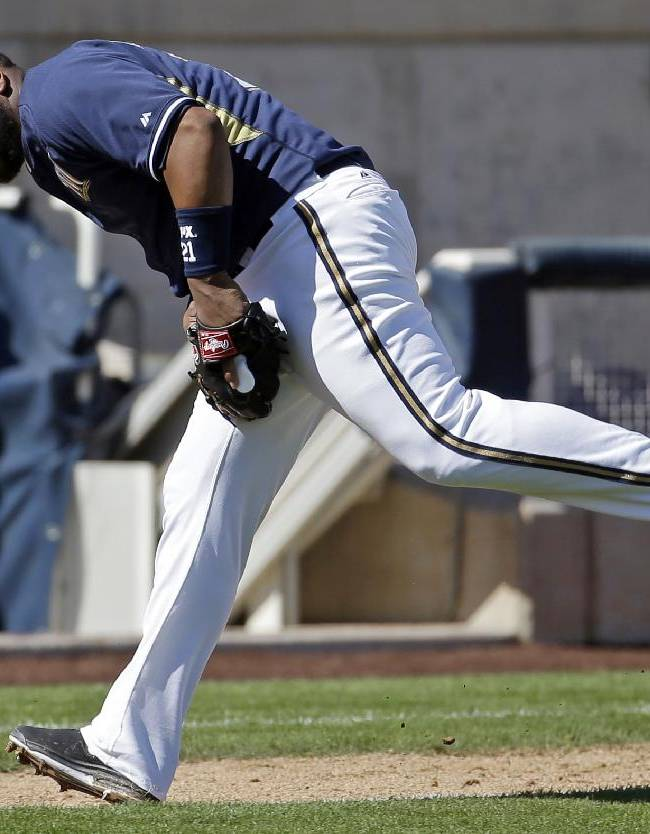 Milwaukee Brewers' Juan Francisco can't handle a ball hit by Oakland Athletics' Jake Elmore during the fourth inning of an exhibition spring training baseball game Wednesday, March 5, 2014, in Phoenix