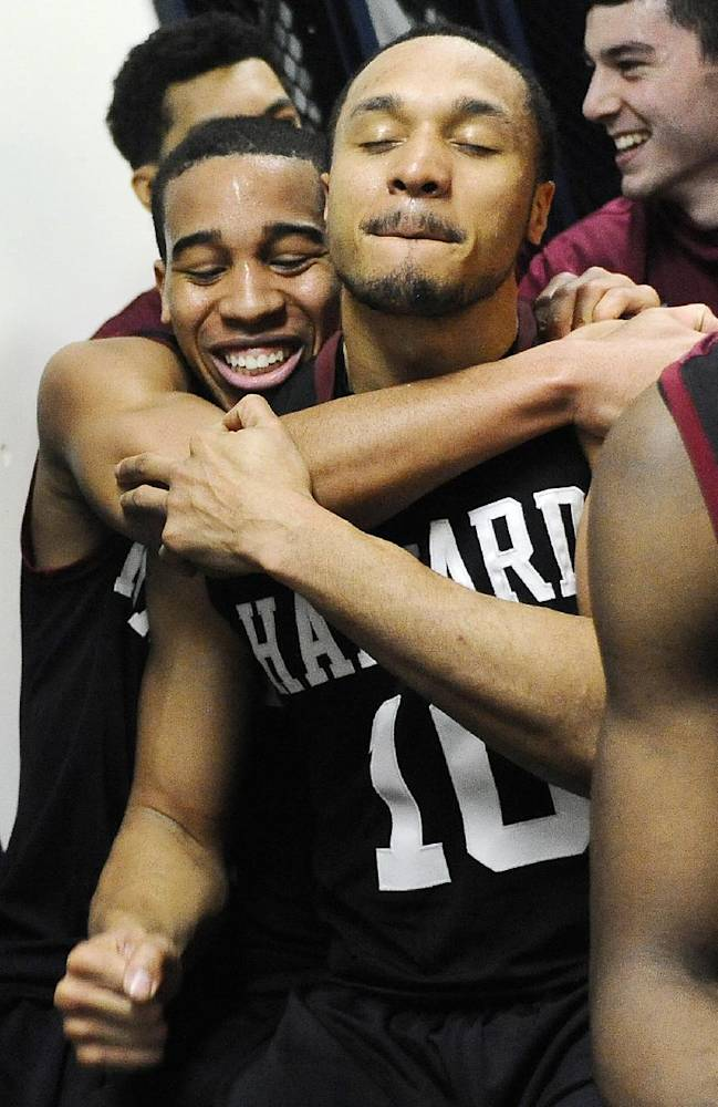 Harvard's Siyani Chambers, left, and Brandyn Curry, right, embrace in the locker room after their 70-58 win over Yale at the end of an NCAA college basketball game, Friday, March 7, 2014, in New Haven, Conn